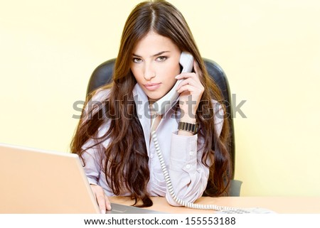Pretty business woman in office having a telephone call - stock photo