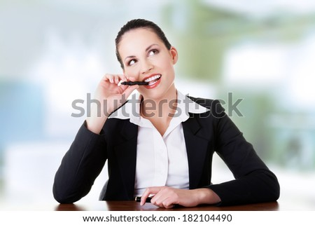 Pretty business woman in sitting at the desk and thinking - stock photo