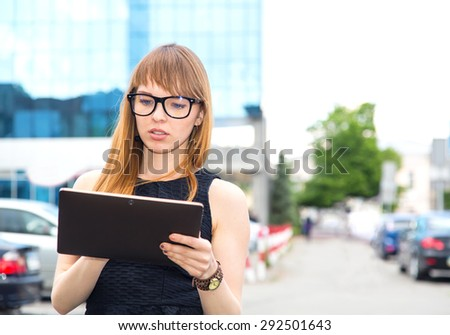 Pretty business woman in working using digital tablet outdoors. Beautiful business woman in glasses on the background of an office building, an electronic tablet computer. Smiling girl. Woman student.