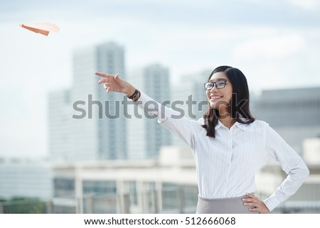 Pretty business woman launching plane in the air