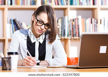 Pretty business woman, wearing in white and black blouse and glasses, sitting at the table with laptop and writing something in her notebook, on the bookshelves background, waist up - stock photo