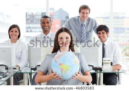 Pretty businesswoman and her team showing a terrestrial globe in the office - stock photo