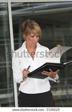 Pretty businesswoman checking her notes before going into the meeting
