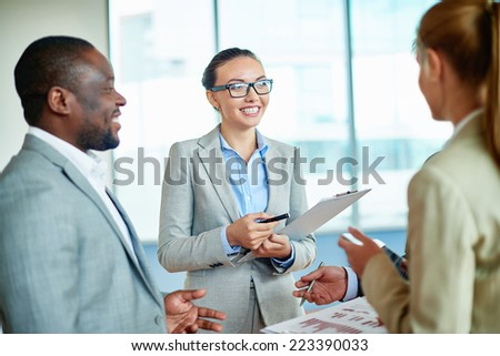 Pretty businesswoman discussing plans or ideas with her colleagues in office