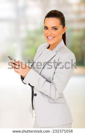 pretty businesswoman holding smart phone - stock photo