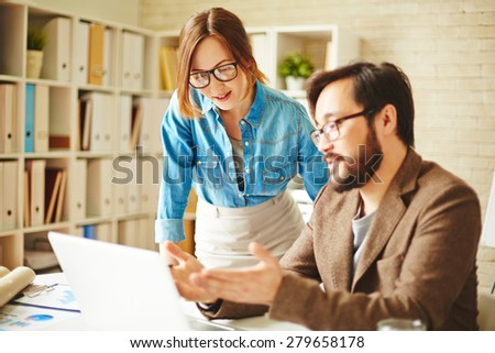 Pretty businesswoman listening to her colleague explanations in office - stock photo