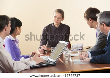 Pretty businesswoman looking at one of her partners during corporate meeting