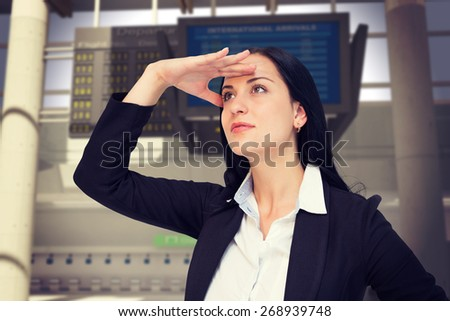 Pretty businesswoman looking with hand up against airport - stock photo