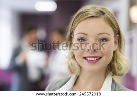 Pretty Businesswoman posing while colleagues talking together in modern office. Looking camera - stock photo