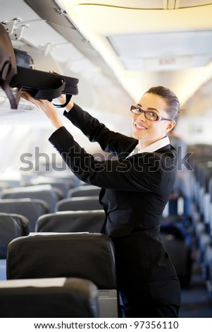 pretty businesswoman putting her luggage into overhead locker on airplane - stock photo