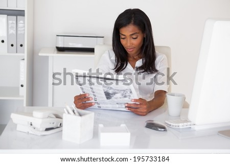 Pretty businesswoman reading newspaper at her desk in her office - stock photo