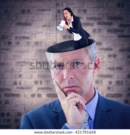 Pretty businesswoman shouting with megaphone against stone wall - stock photo
