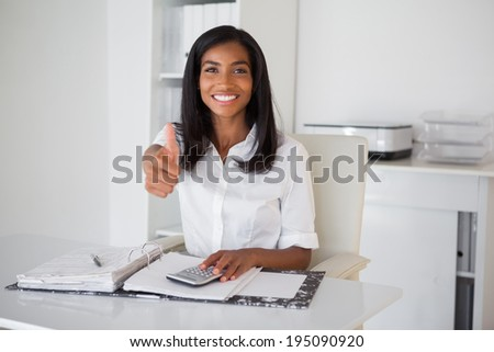 Pretty businesswoman showing thumb up to camera at her desk in her office