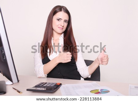 Pretty businesswoman showing thumb up to camera at her desk in her office  - stock photo