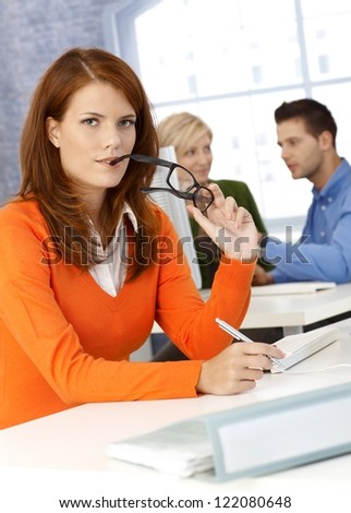 Pretty businesswoman sitting at desk with glasses and pen handheld, looking at camera. - stock photo