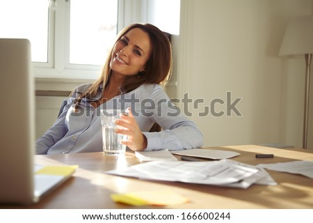Pretty businesswoman sitting at her desk with a glass of water looking at camera smiling. Confident young caucasian woman working from home office. - stock photo