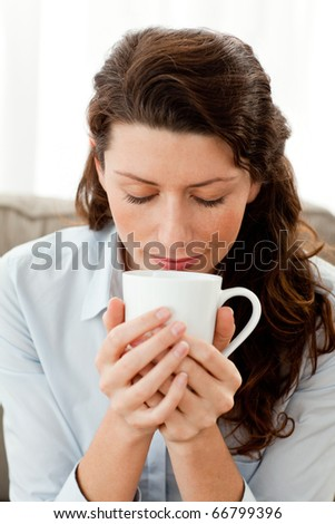 Pretty businesswoman smelling her coffee sitting on the sofa at home