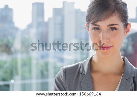 Pretty businesswoman smiling at camera beside large window - stock photo