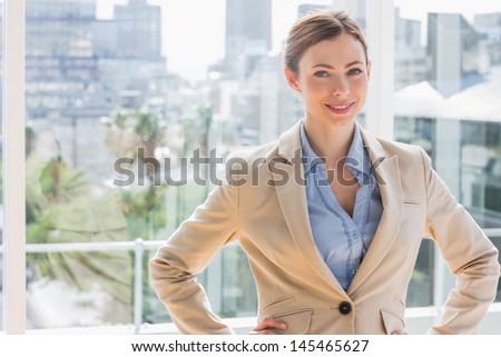 Pretty businesswoman smiling at camera with hands on hips by large windows
