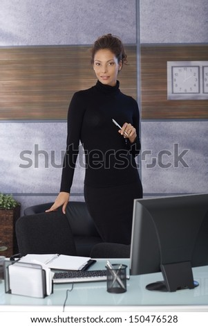Pretty businesswoman standing by desk in office in black outfit.