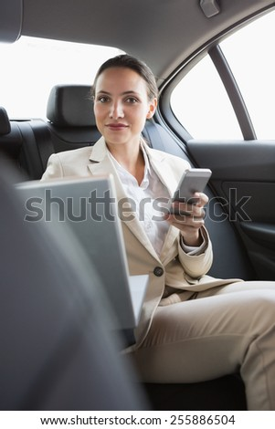Pretty businesswoman working in the back seat in her car - stock photo
