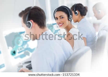 Pretty call center worker using futuristic interface hologram smiling at camera in office - stock photo