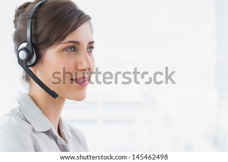 Pretty call centre agent smiling in an office - stock photo