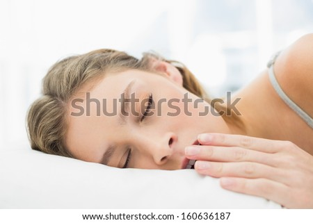 Pretty calm woman lying in her bed yawning with closed eyes