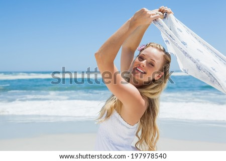 Pretty carefree blonde posing on the beach with scarf on a sunny day - stock photo