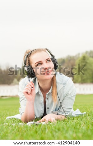 Pretty carefree girl listening music during recreation time in the park on a summer day - stock photo