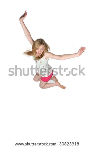 pretty, carefree young woman jumping for joy - stock photo