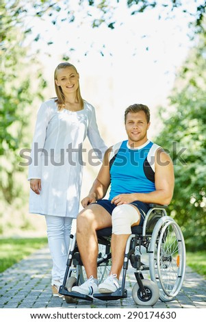 Pretty caregiver walking with male patient in a wheelchair in park