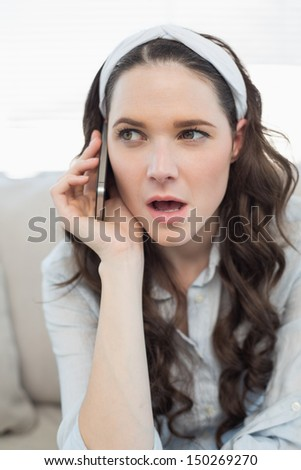 Pretty casual woman being surprised on the phone while sitting on a cosy couch - stock photo