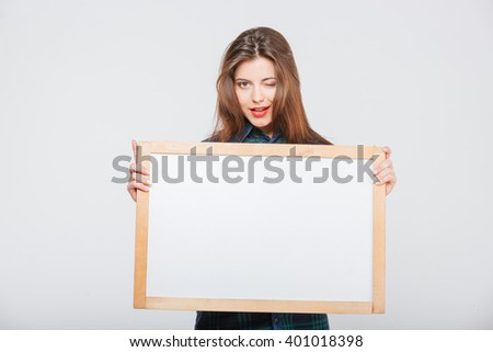 Pretty casual woman holding blank board and winking isolated on a white background - stock photo
