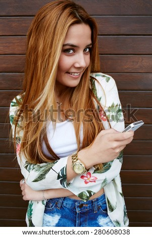 Pretty casually-dressed female hipster chatting on her smart phone and looking to you with brightly smile, happy young woman send text message on her cellphone while standing on wooden wall background - stock photo