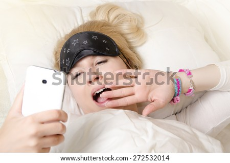 Pretty Caucasian blonde girl waking up and looking at smart phone while yawning - stock photo