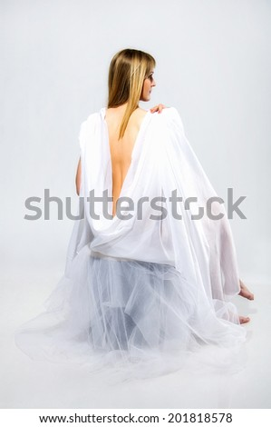 Pretty caucasian blonde young woman is sitting on white background dressing white cloth with naked back and barefoot