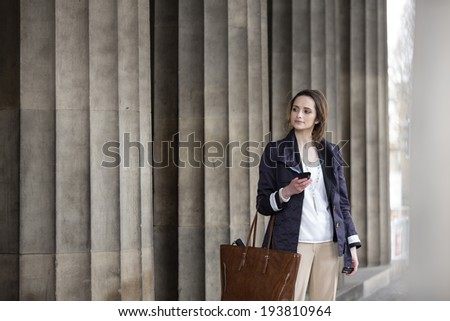 Pretty Caucasian business woman looking at mobile smartphone in front of courthouse. - stock photo