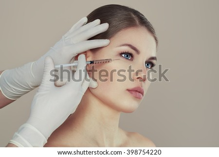 Pretty Caucasian female having injection in eyes zone. Male doctor with syringe filling woman's face with collagen. Rejuvenation therapy concept.   - stock photo