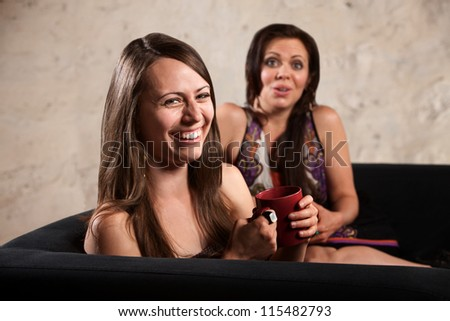 Pretty Caucasian females on sofa laughing together