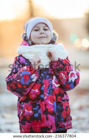 Pretty Caucasian girl in winter clothes standing outdoor. White scarf and hat - stock photo