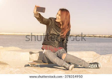 Pretty Caucasian girl is taking a selfie on her skateboard outdoor - concept about sport, people and technology
