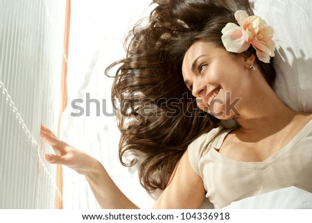 Pretty Caucasian girl lying on a pillow on a light background - stock photo