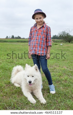 Pretty Caucasian girl standing on green grass with laying beside white dog