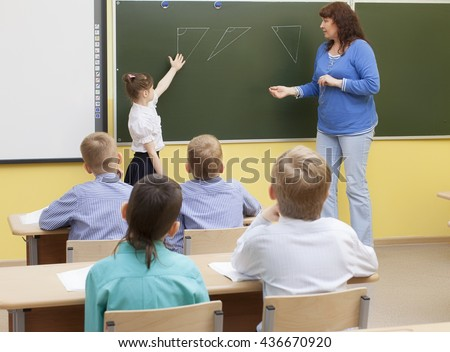 Pretty caucasian girl student of primary school show on the pictures on the classroom blackboard triangle. Nearby is a teacher. Mature Caucasian woman. Brunette - stock photo
