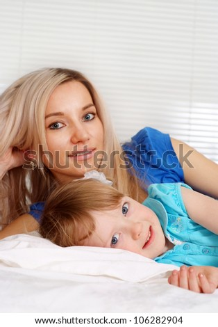 Pretty caucasian mother and daughter lying on the bed