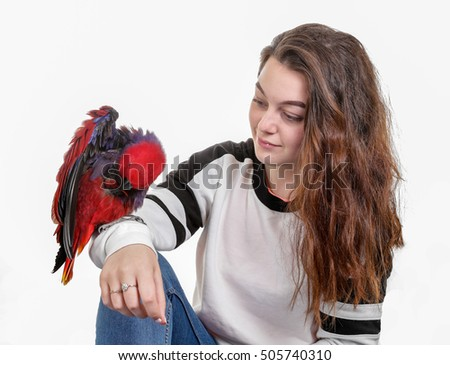 Pretty caucasian teenage girl with a pretty red parrot on her arm