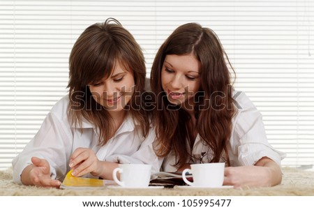 Pretty Caucasian two women lying on the carpet with cups