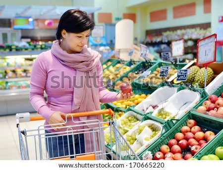 pretty caucasian woman choosing apple during shopping at fruit vegetable supermarket - stock photo