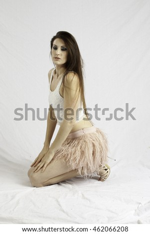 Pretty Caucasian woman in a pink dress, sitting thoughtfully